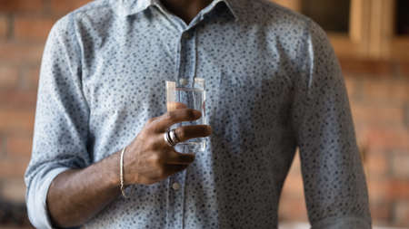 Crop close up of African American man hold glass recommend drinking clean pure mineral still water for body refreshment. Biracial guy follow healthy lifestyle. Wellness, hydration, diet concept. Zdjęcie Seryjne