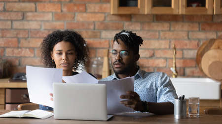 Focused African American young family tenants sit in kitchen manage household budget using computer. Concentrated biracial couple consider financial paperwork, pay bills online on laptop together.