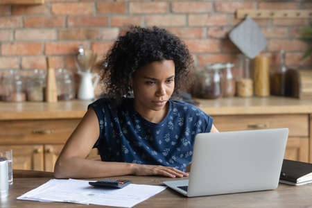Focused young African American woman sit at desk at home look at laptop screen manage household budget. Serious biracial female calculate finances expenditures, pay bills taxes online on computer. Foto de archivo