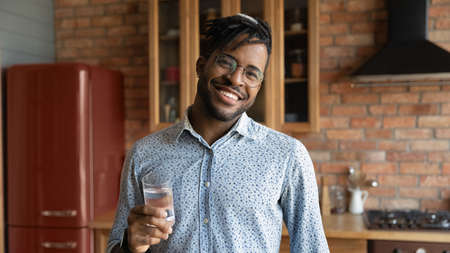Portrait of smiling young African American man pose at home kitchen hold glass with pure clear still mineral water. Happy 20s biracial guy recommend aqua for body refreshment. Hydration concept.