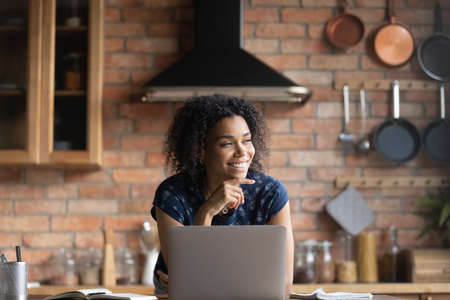 Happy young African American woman distracted from computer work look in distance visualizing or dreaming. Smiling biracial female use laptop at home office, lost in thoughts thinking or planning. 免版税图像