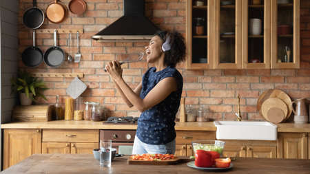 Overjoyed millennial African American woman have fun cooking healthy tasty breakfast in home kitchen. Happy playful young biracial girl sing entertain enjoy good morning prepare food at countertop. Zdjęcie Seryjne
