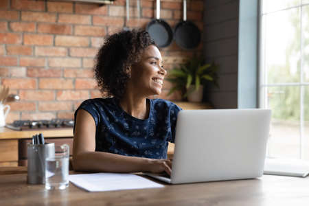 Smiling young biracial woman work on laptop at home office look in distance dreaming or visualizing. Happy African American female use computer feel distracted thinking or planning. Vision concept. 免版税图像