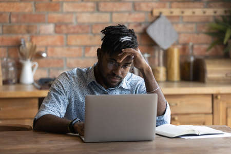 Unhappy 20s biracial man sit at home kitchen look at laptop screen frustrated by gadget problems. Mad young African American male distressed by slow internet connection, spam or computer breakdown.