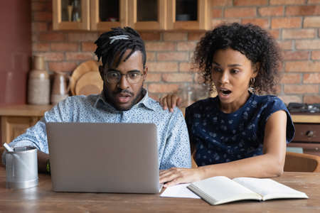 Shocked African American couple look at laptop screen frustrated by debt email paying bills online. Stunned biracial man and woman surprised by unexpected bad unpleasant news online on computer. Archivio Fotografico