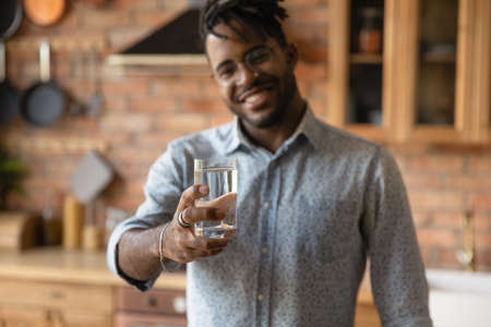 Close up blurred background of smiling African American man hold glass recommend drinking clear clean pure mineral water. Happy biracial male follow healthy lifestyle. Hydration, dieting concept.