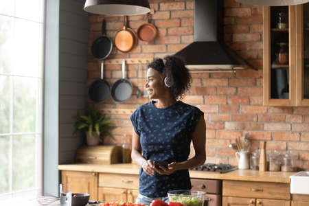Happy young African American woman in headphones listen to music on cellphone cooking at home. Smiling 20s biracial female enjoy good sound in earphones and smartphone, prepare food in kitchen.