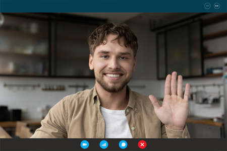 Head shot portrait device screen view smiling man waving hand and looking at camera, greeting friends or relatives, making video call, chatting online, using webcam and social media app at home