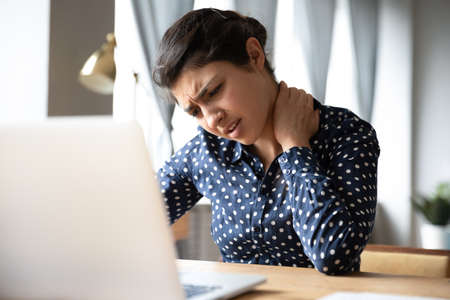 Pinched nerves, tensed sore muscles, fibromyalgia ache due sedentary lifestyle and incorrect posture concept. Indian ethnicity frowning woman sitting at desk in front of laptop, touch neck feels pain Reklamní fotografie