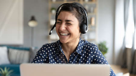 Cheerful Indian female wear headset with microphone sit in front of laptop laughing during video call communication. Distance e-learning, helpline work technical support happy worker portrait concept