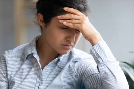 Close up image upset indian woman closed eyes touch forehead with hand feels unwell severe head ache migraine imbalance. Pregnancy decision about abortion, divorce and break up, life troubles concept