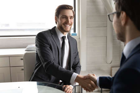 Smiling young male job seeker shaking hands with employer hr manager, making good first impression after successful job interview in office. Happy two businessmen celebrating making agreement. Standard-Bild