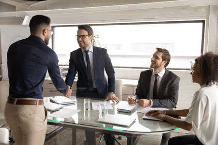 Happy 30s caucasian businessman shaking hands, welcoming young arabian ethnic partner at brainstorming meeting with smiling diverse multiracial colleagues in modern international company office.