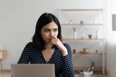 Pensive young Vietnamese woman work on computer in home office look in distance thinking pondering of problem solution.