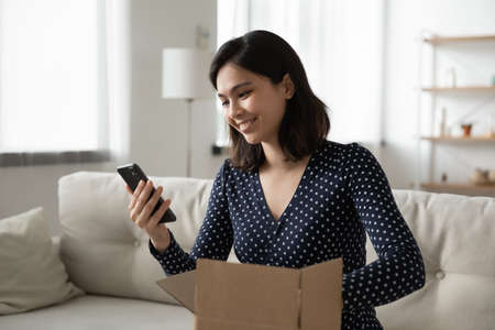Smiling young asian woman unbox cardboard package parcel shopping online on smartphone gadget.