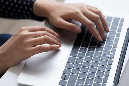 Close up top view of woman typing texting on modern laptop keyboard at home office.
