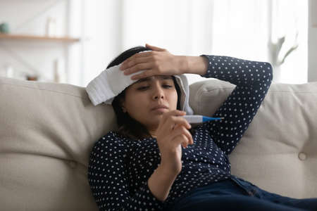 Unhealthy millennial asian girl sit on couch at home feel unwell sick suffer from covid-19 coronavirus symptoms.