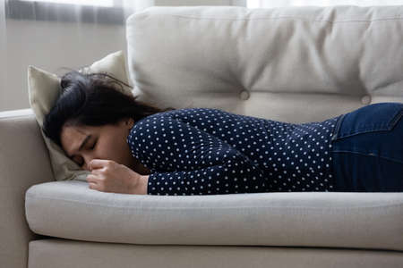 Upset young woman lying sleeping on sofa in living room suffer from abortion or miscarriage. Unhappy female relax on couch at home feel depressed stressed with problems. Depression concept.