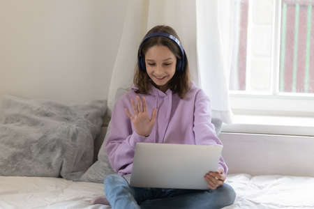 Smiling teen girl in headphones sit on bed at home look at laptop screen speak talk on video call. Happy Caucasian teenager in earphones have fun engaged in webcam digital conversation on computer.
