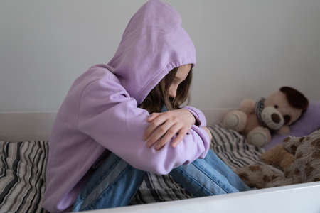 Sad lonely teenage girl sit on bed at home cover hide in hood suffer from school bullying or discrimination. Unhappy distressed teen child struggle with loneliness solitude. Loner, outcast concept.