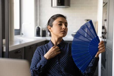 Overheated Indian woman feel unwell wave with hand fan suffer from hot weather no air condition at home. Unhealthy ethnic female feel dehydrated have heatstroke, struggle with hormonal imbalance.