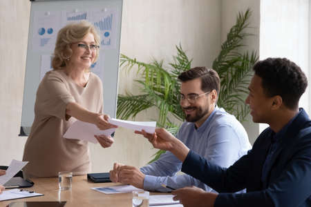 Smiling middle-aged female trainer or coach lead meeting or training in office share handout materials to employees. Happy businesswoman give document paperwork to diverse workers at briefing.