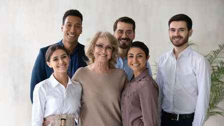 Portrait of smiling multiracial businesspeople pose together at workplace show leadership. Happy diverse multiethnic employees with middle-aged female boss demonstrated unity and support in office.