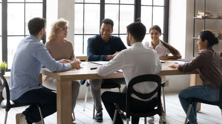 Smiling diverse multiracial businesspeople sit at desk in office discuss ideas at meeting together. Happy multiethnic colleagues have fun laugh brainstorming in group at briefing. Teamwork concept.