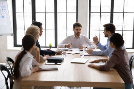 Young Caucasian businessman head lead meeting with multiracial diverse employees in office. Multiethnic businesspeople talk brainstorm discuss business ideas at team briefing. Teamwork concept.