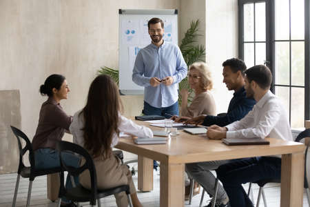 Smiling young male coach make whiteboard presentation at meeting with diverse colleagues in office. Happy speaker or trainer present project on flip chart to employees discussing. Teamwork concept. 版權商用圖片