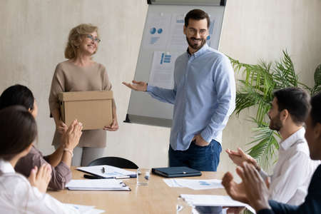 Smiling young businessman introduce middle-aged newcomer newbie at meeting in office. Happy male boss or director welcome new employee worker to team, colleagues applaud. Recruitment concept.