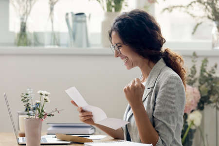 Excited young Caucasian woman sit at desk read good pleasant news in paper letter feel euphoric. Happy overjoyed millennial female employee receive promotion notice in post paperwork correspondence.