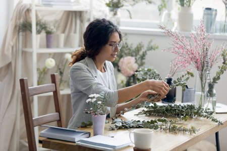 Creative millennial female designer sit at desk in modern home office compose arrange plants flowers in bouquets. Young Caucasian woman florist make floral decorations or compositions for sale.