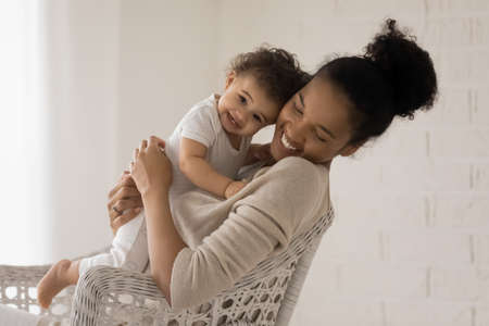 Happy young African American mom hold lean to chest cuddle little newborn baby relax in chair at home together. Smiling biracial mother embrace hug ethnic small toddler daughter show love care.