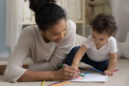 Caring happy African American mom lying on floor at home drawing with little baby infant. Loving smiling biracial mother feel playful paint engaged in funny activity with small toddler child.