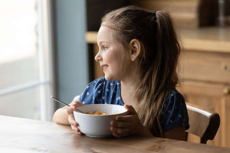 Happy little 6s girl sit at table at home kitchen eat healthy cereals with milk look in distance dreaming or thinking. Smiling small kid child have delicious tasty nutritious breakfast. Diet concept.