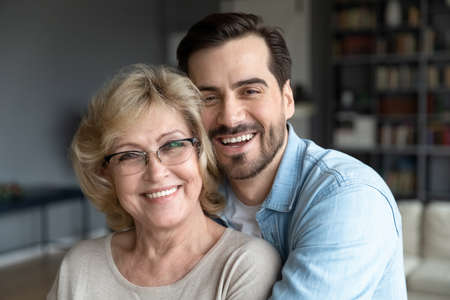 Head shot close up portrait of loving young bearded man cuddling smiling beautiful middle aged mature mother on eyeglasses. Loving different generations family looking at camera, enjoying weekend.