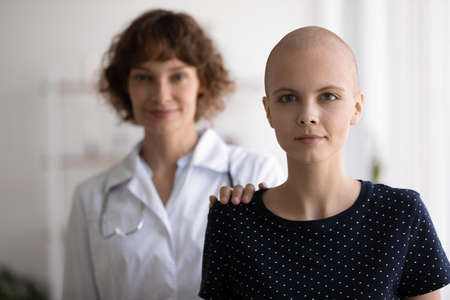 Head shot portrait hairless woman standing with doctor behind back, looking at camera, struggling with oncology disease, cancer, specialist nurse supporting patient, touching shoulder.