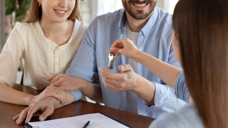 Happy houseowners. Close up of female real estate agent, broker or realtor holding in hand bunch of keys of new house flat apartment. Stok Fotoğraf