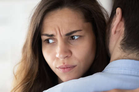 Close up view of frustrated young woman hugging husband and looking aside trying but having no power to forgive cheating lie betrayal