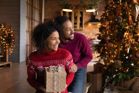 Dreamy smiling African American couple hugging, looking to aside, making Christmas wish, dreaming about future, happy young woman holding gift box, family celebrating New Year at home together