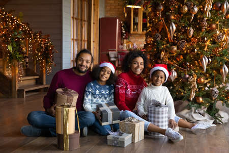 Portrait happy African American family wearing festive red caps and warm sweaters celebrating Christmas, smiling parents with daughter and son sitting on warm floor with gift boxes, looking at camera