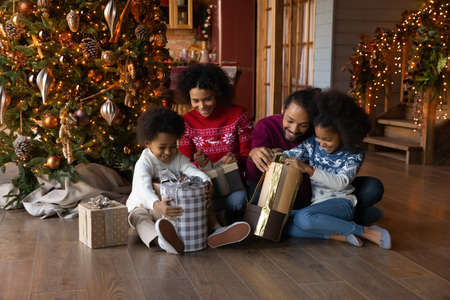 Happy African American family with two kids unpacking gifts on Christmas eve, smiling mother and father with little daughter and son wearing sweaters sitting on floor near festive tree at home Stok Fotoğraf
