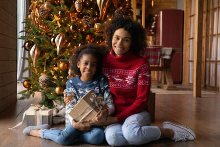 Portrait smiling African American mother and adorable daughter hugging, holding gift box, looking at camera, happy mum and little girl sitting on warm floor near Christmas tree at home, celebrating