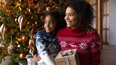 Close up dreamy African American woman with adorable daughter looking to aside, holding gift box, sitting near festive tree, happy mother hugging little girl, making wish on Christmas eve Stok Fotoğraf