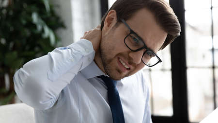 Close up head shot unhappy young male manager entrepreneur in eyeglasses massaging inflamed neck, suffering from strong backpain, feeling tensed muscles ache due to daily sedentary office work.