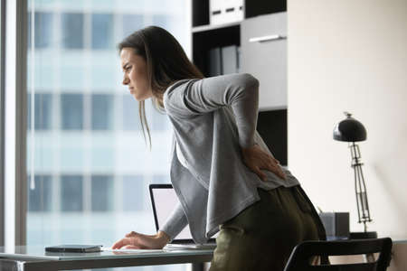 When office chair is uncomfortable. Sad suffering millennial woman employee leaning forward above work desk holding hand on lower back feeling bad, sudden pain attack, trying to massage tensed muscles