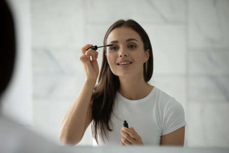 Long thick eyelashes. Happy inspired millennial female spending time by mirror making herself up using facial decorative cosmetics holding applicator putting liquid black waterproof mascara on lashes Foto de archivo