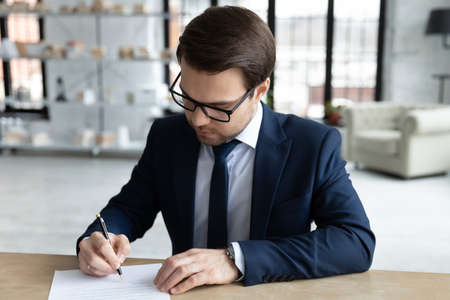 Focused young businessman in formal wear and eyeglasses doing corporate paperwork, putting signature on financial or legal documents or closing deal by signing contract, sitting at table in office.