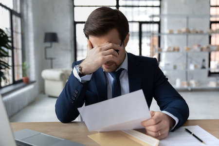 Frustrated 30s employee in formal wear holding paper dismissal notice, unhappy confused young businessman feeling stressed about bad news in letter, company bankruptcy or financial problems.